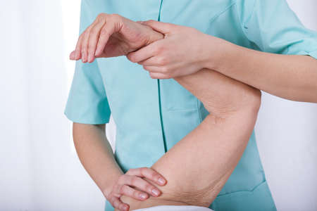 fisioterapia: Fisioterapeuta practicar movimientos pasivos de flexi�n del codo