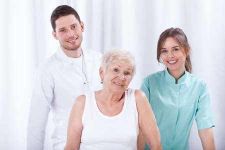 physiotherapists: Happy geriatric patient with her young physiotherapists