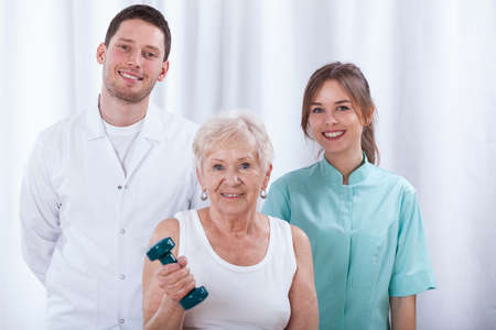 physiotherapists: Adult woman training in hospital with her physiotherapists Stock Photo
