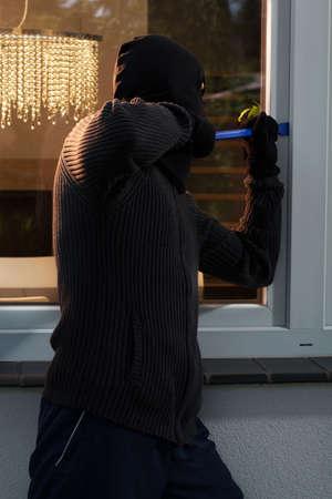 swindler: Vertical view of burglar opening the window Stock Photo