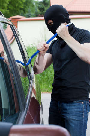 loot: Thief in balaclava breaking into the car Stock Photo