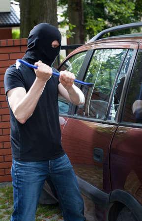 Vertical view of burglar smashing car glass photo