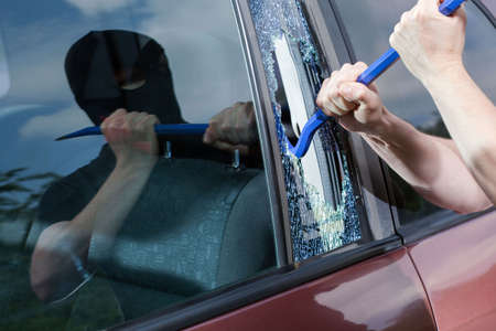 criminals: Robber with crowbar smashing the glass, horizontal Stock Photo