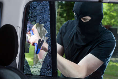 car glass: Car thief with crowbar and broken glass Stock Photo