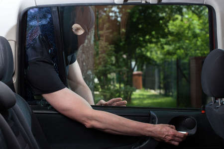 Horizontal view of burglar opening car door photo