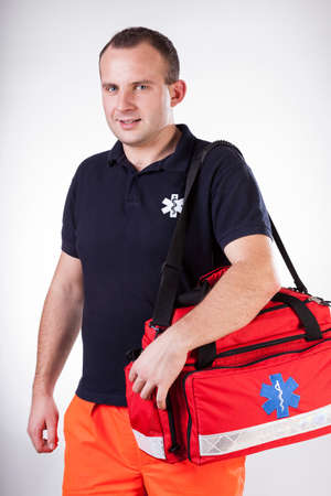 Rescuer with first aid kit going to help patient