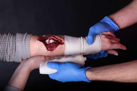 Closeup of paramedic dressing a  wound