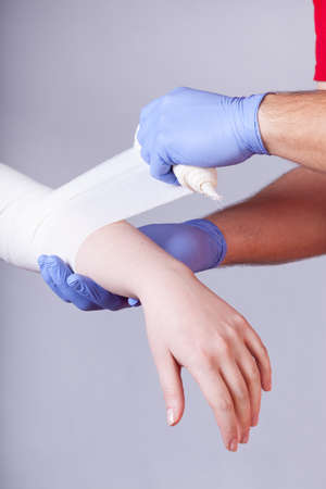 paramedical: Closeup of paramedical bandaging forearm of woman
