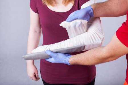 paramedical: Paramedical bandaging broken arm of young woman