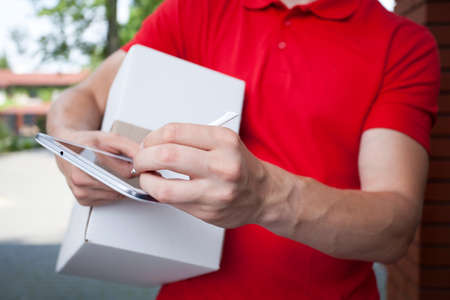 handheld computer: Close-up of a courier using tablet at work Stock Photo