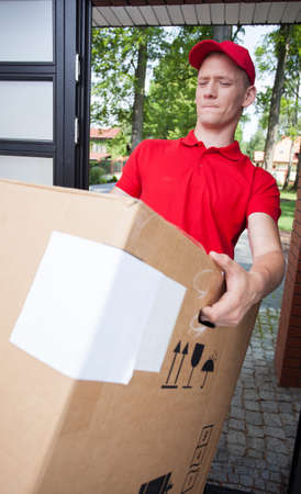delivery service: Young delivery man holding a heavy box