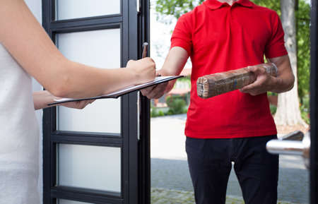 Close-up of a woman receiving a package from delivery man Standard-Bild