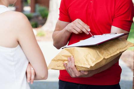 Primo piano di un uomo di consegna che chiede una firma
