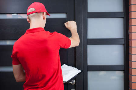Back view of a delivery man knocking on the client's door