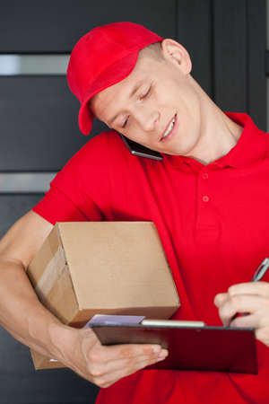 Busy courier calling on mobile phone and writing on clipboard photo