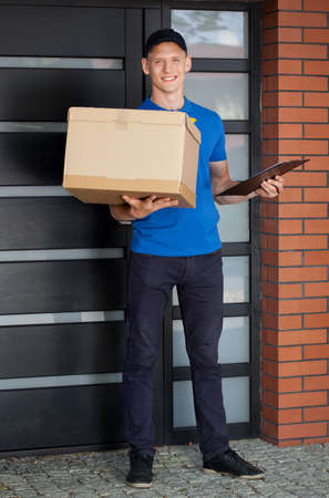 Smiling courier holding cardboard box and clipboard photo