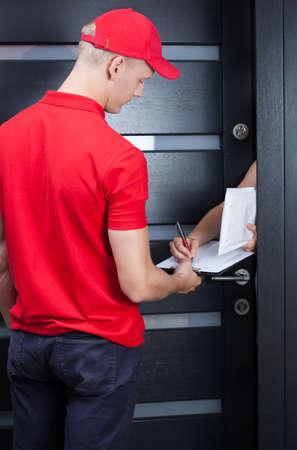 Courrier en uniforme rouge en attente d'une signature Banque d'images - 30662667