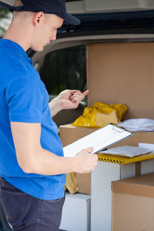 Young delivery man looking at clipboard, vertical photo