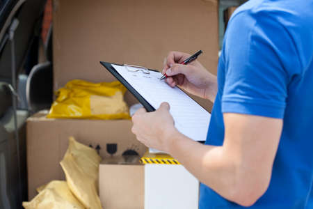 freight transportation: Close-up of a couriers hand writing on clipboard Stock Photo