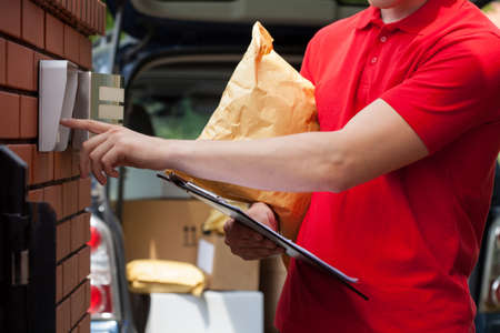 Close-up of a courier with packages dialing intercom Stockfoto