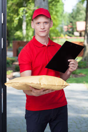 bringing: Handsome young courier bringing a package, vertical
