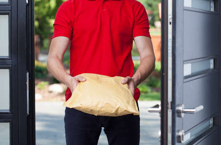 Close-up of a delivery man giving a package photo