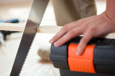 serrucho: Las manos del hombre utilizando un serrucho durante la renovación, horizontal Foto de archivo
