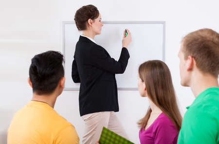 Female teacher writing on whiteboard at classroom photo