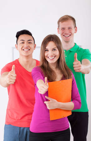 Happy students showing thumbs up sign, vertical photo