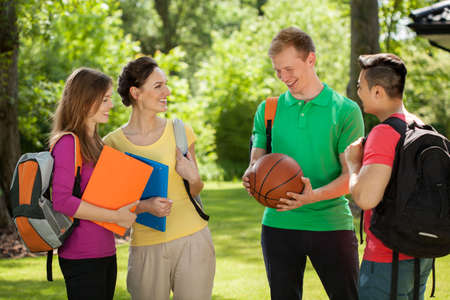 international basketball: Horizontal view of a group of students talking outdoors