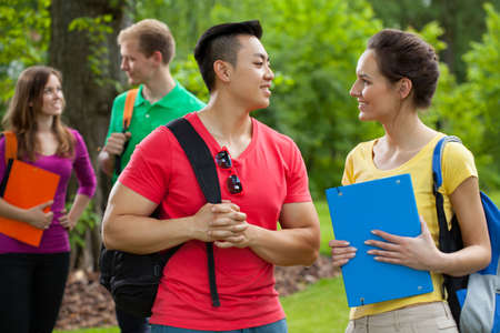 Multi-ethnic students with folders and backpacks outdoors photo