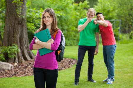 teasing: Teenage boys laughing behind girls back, horizontal