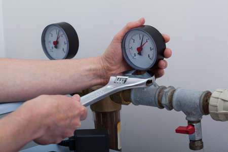 pressure gauge: Plumber during work with a wrench, horizontal Stock Photo