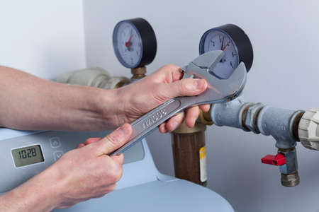 Mans hands with wrench repairing pressure gauge photo