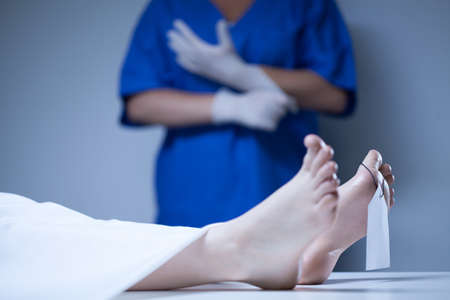 toe tag: Labeled body of the deceased lying in mortuary Stock Photo
