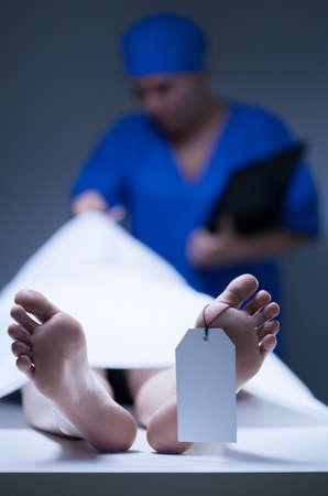 toe tag: Worker of morgue making posthumous procedures