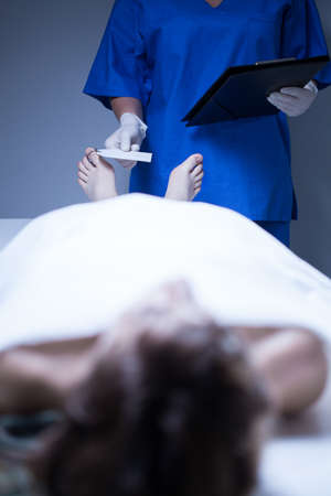 toe tag: Worker of morgue labeling of corpse of young woman