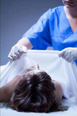 女性の死体を覆う遺体安置所の労働者