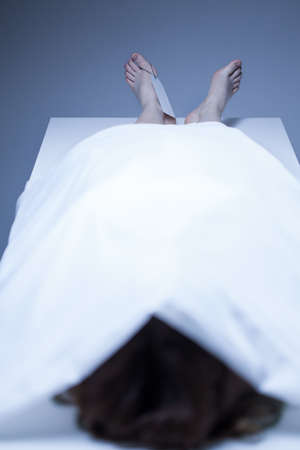 Dead body of woman covered by white sheet