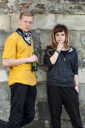 joven fumando: Dos rebeldes j�venes bebiendo y fumando Foto de archivo