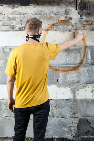 troublemaker: Young hooligan drawing a graffiti on the wall