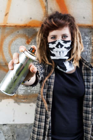rebellious: Young female hooligan holding graffiti spray in hand