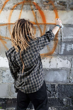 troublemaker: Young vandal drawing graffiti on the wall Stock Photo