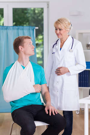 splint: Patient using sling and doctor in surgery Stock Photo