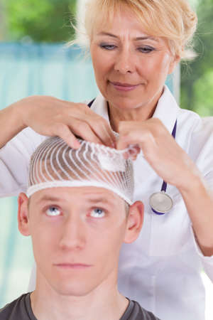 concussion: Closeup of doctor applying dressing after head injury Stock Photo