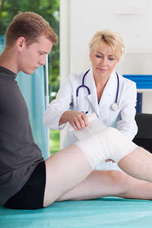 lower limb: Vertical view of doctor bandaging runners knee Stock Photo