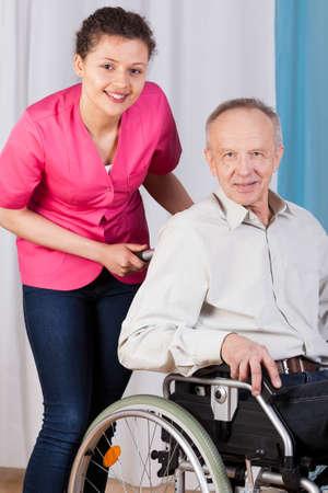 車椅子および看護婦にシニアのクローズ アップ 写真素材