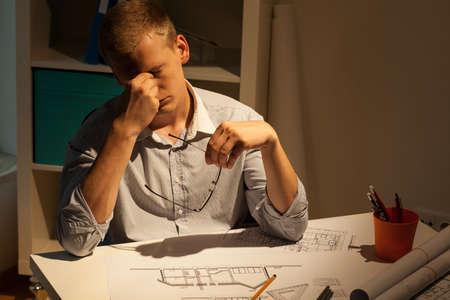 Horizontal view of tired architect at night photo