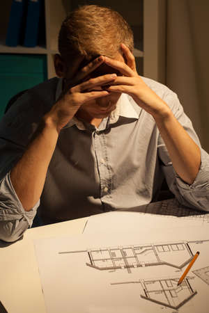 Architect making a project at night, vertical photo