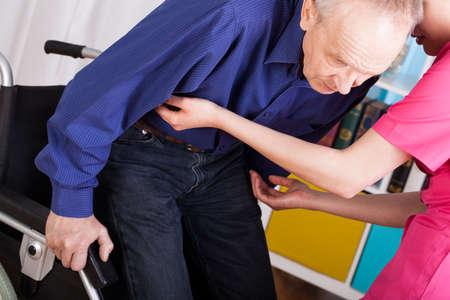 Geriatric patient sitting on wheelchair with help of nurse